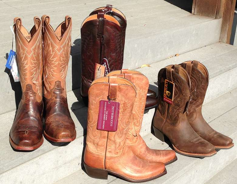 four pairs of cowboy boots on steps, two a lighter brown and two a darker brown