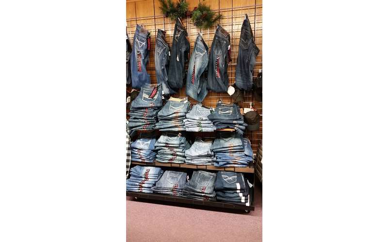 display of jeans stacked on racks and hanging from hooks