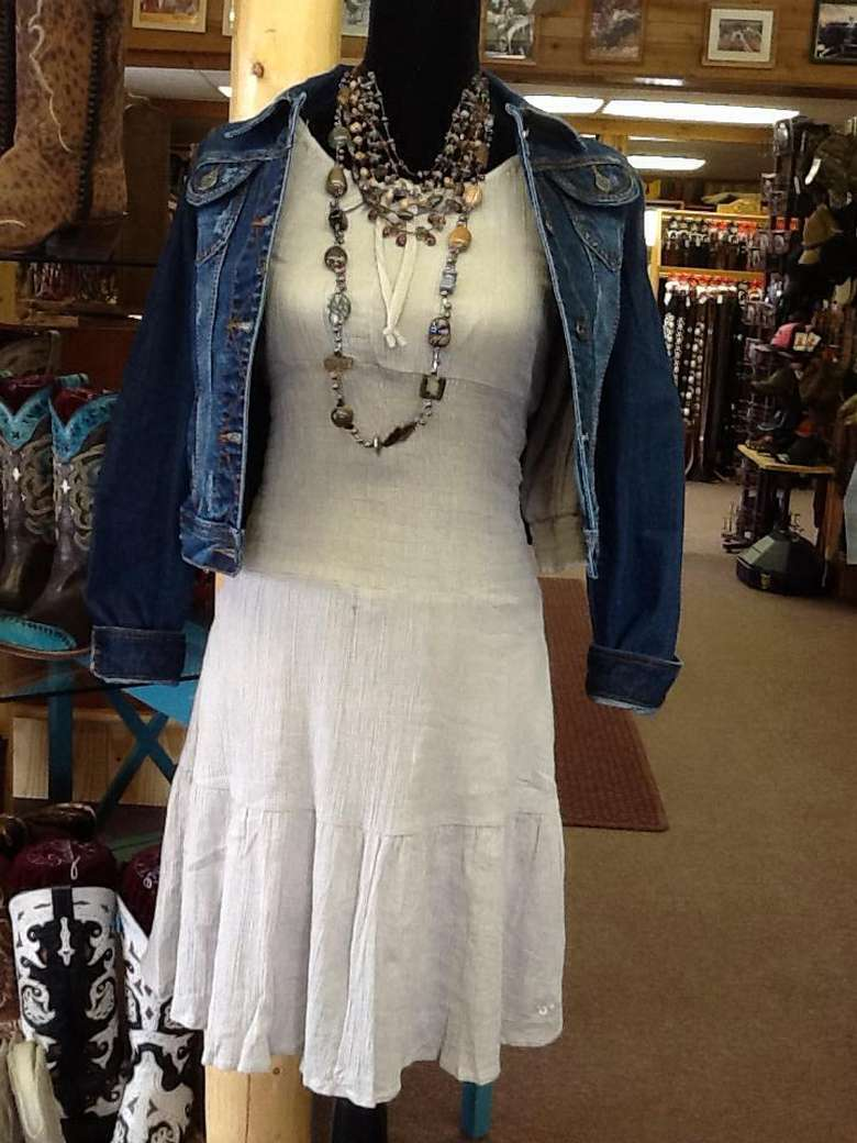 white cotton dress on display with denim jacket and chunky necklaces
