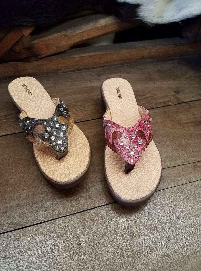 two different sandals, left feet, western-style, one navy blue and the other a dark pink
