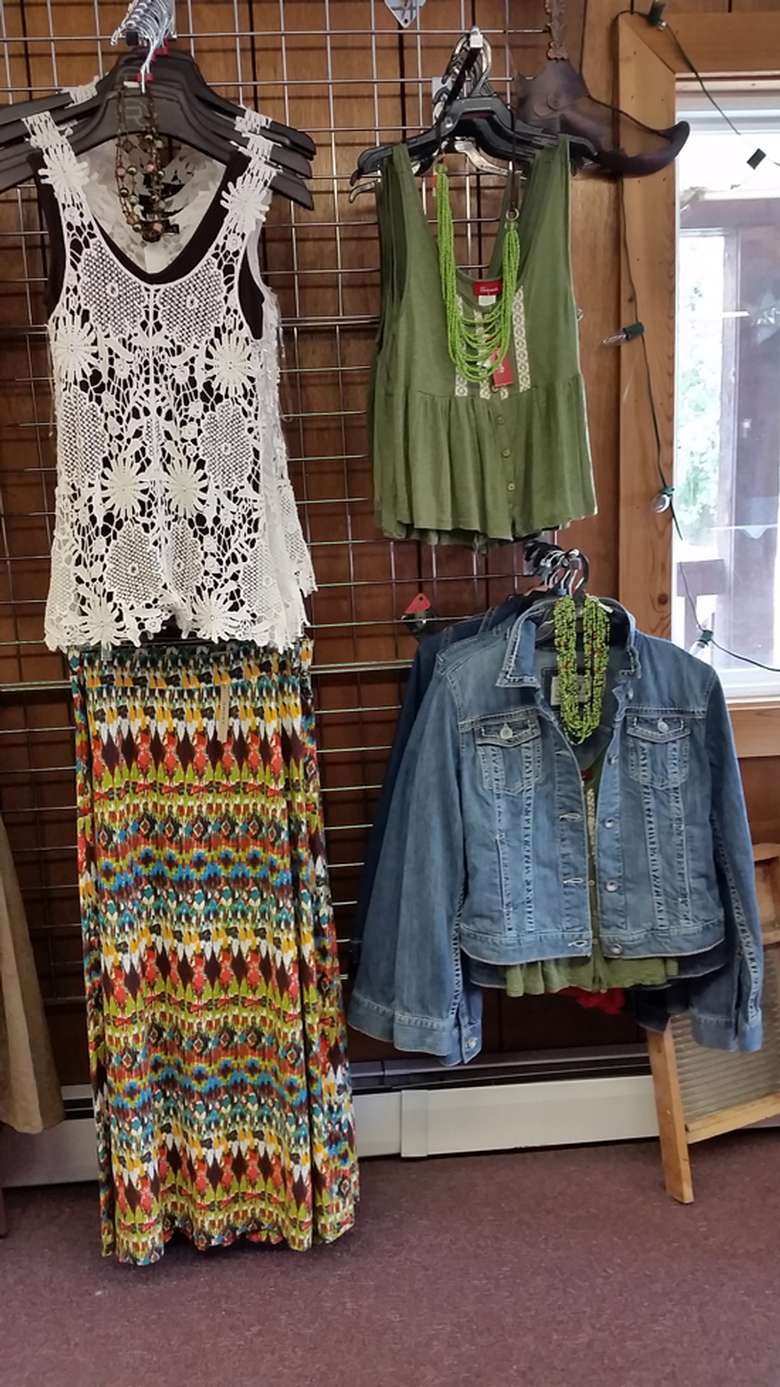 women's clothes hanging on display - a white sleeveless floral top, a colorful long skirt, a green sleeveless top with a green necklace, and a denim green jacket with a green necklace