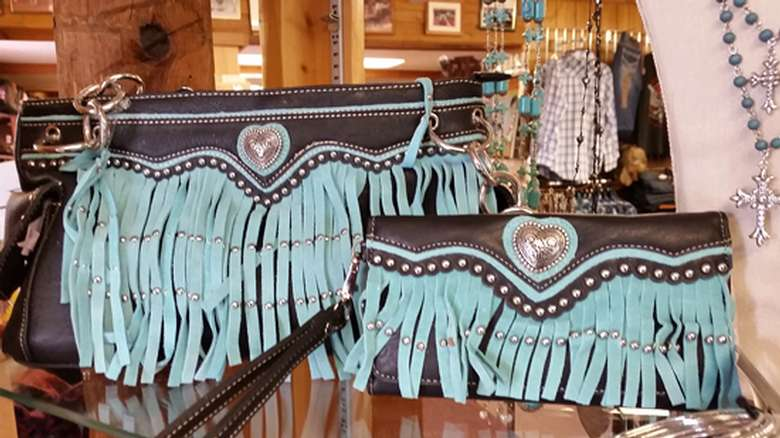 two clutch handbags that are identical except one is bigger, turquoise and dark brown with a heart