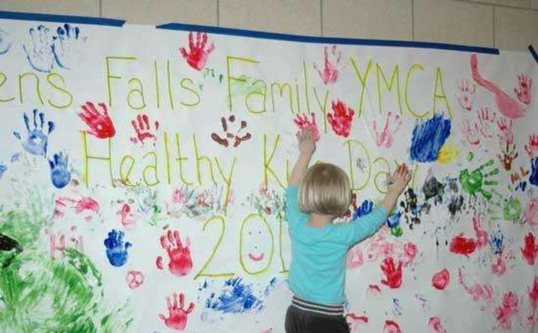 Healthy kids day painted sign with girl making hand prints