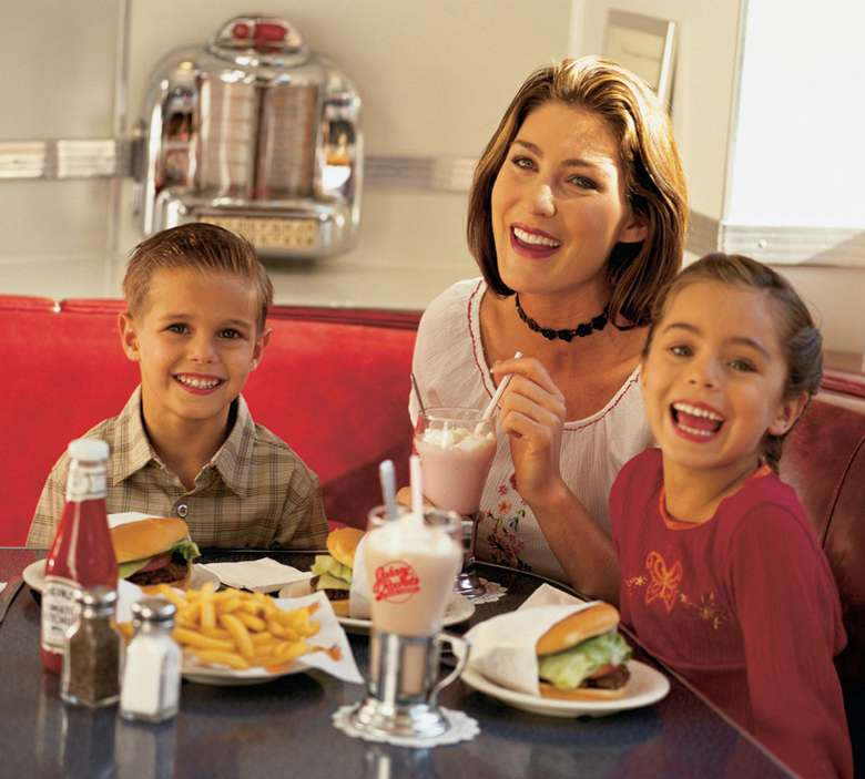 mother and two kids eating burgers and milkshakes