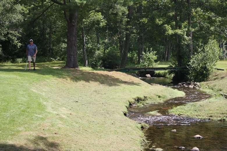 golfer near a small brook