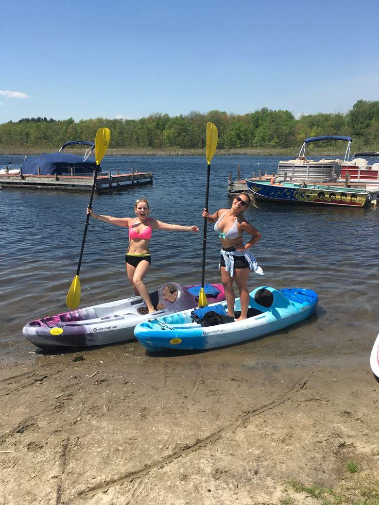 two women getting ready to launch kayaks