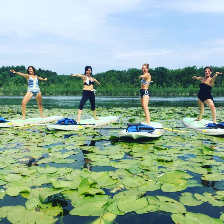 four women doing SUP yoga in a patch of lillypads
