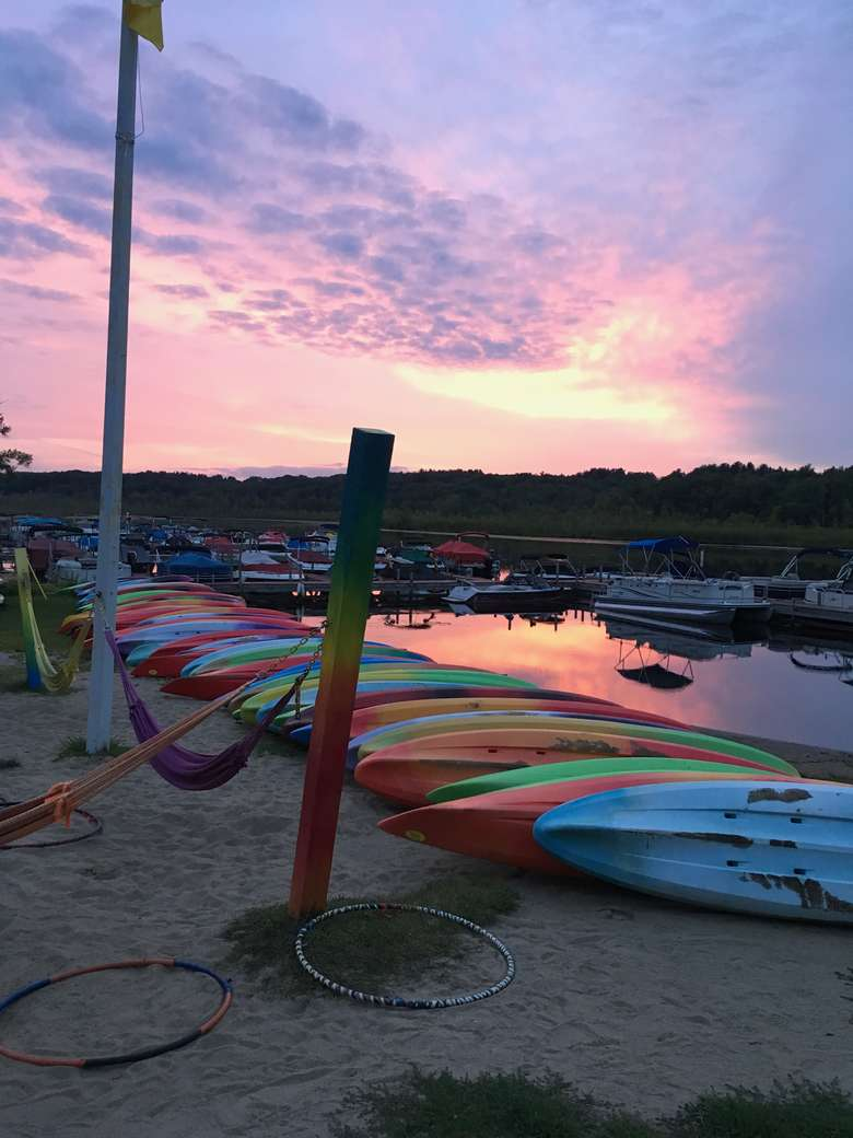 row of colorful kayaks at sunset