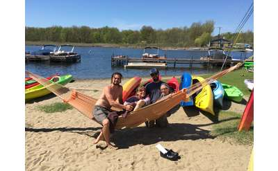 four people posing in a hammock with colorful kayaks in the background