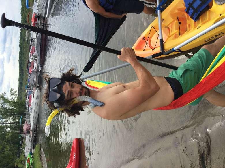 man wearing a scuba mask holding a SUP paddle