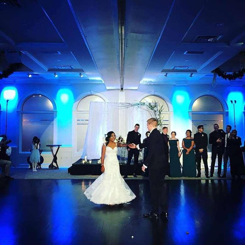 bride and groom on dance floor, guests watching