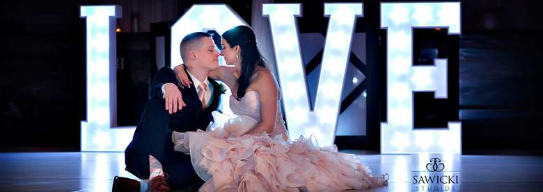 bride and groom kissing, the word love spelled out behind them