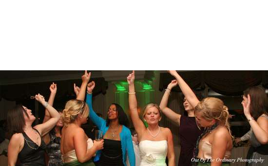 a group of women at a wedding dancing with their arms up