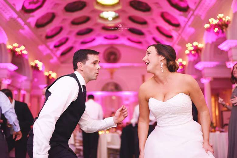 bride and groom dancing, there's pink up lighting on the walls
