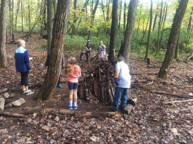 kids making a small structure in the woods