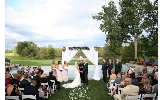 a couple saying their vows in front of guests on the golf course