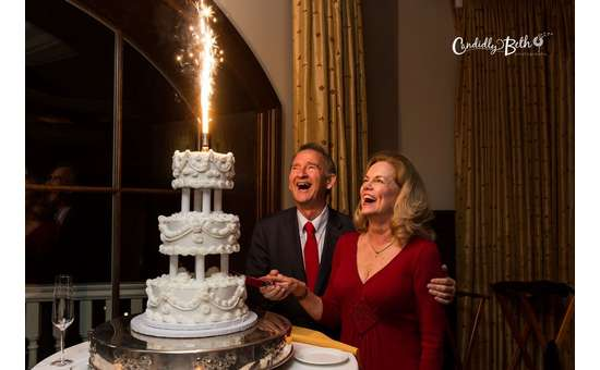 bride and groom looking at a sparkler shooting flames out of a cake