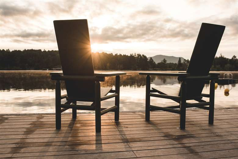 two Adirondack chairs on the dock