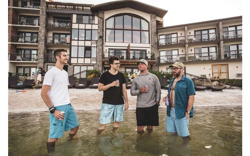 four guys standing in the lake in front of the Golden Arrow drinking beer