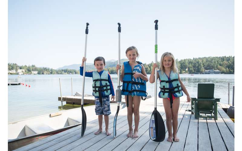 three kids on the dock with paddles