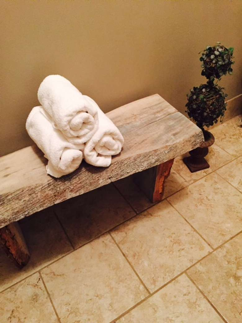 three rolled up towels on a bench