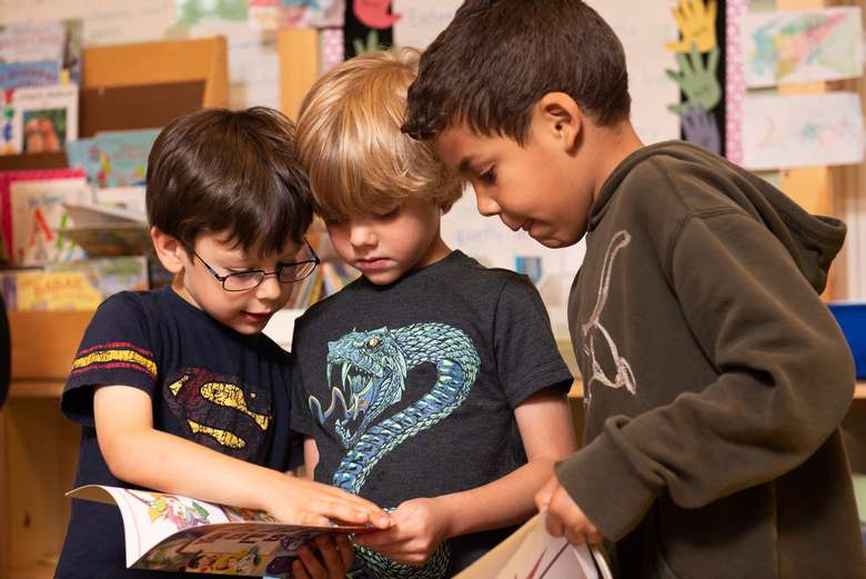 three boys reading a book
