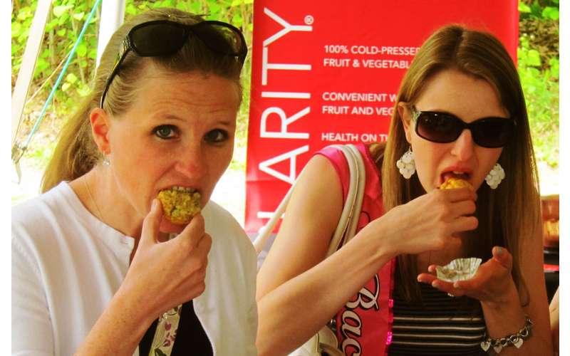 two women taking bites of food
