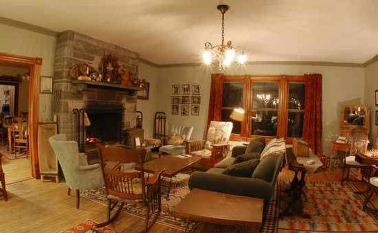 living room with large windows, couch, chairs and fireplace