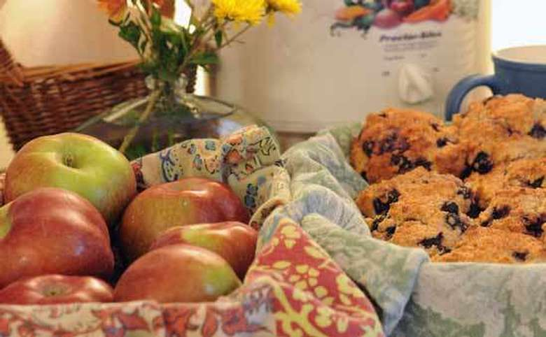 a basket of apples and a basket of blueberry muffins
