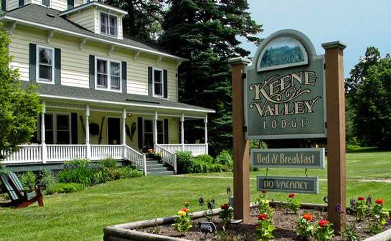 exterior front view of keene valley lodge showing sign and front porch