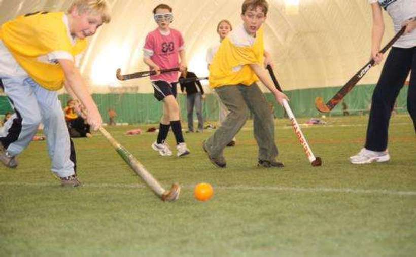 young kids playing field hockey inside a sports complex