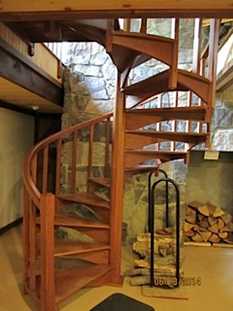 spiral staircase with piles of firewood next to it