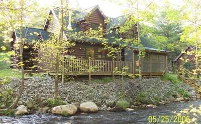 two-story log house in the woods next to a creek