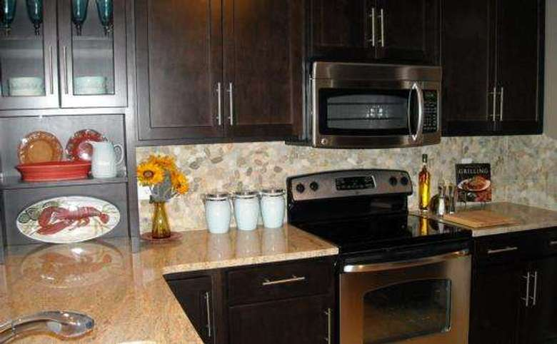kitchen with dark cabinets, stone countertops, and a tiled backsplash