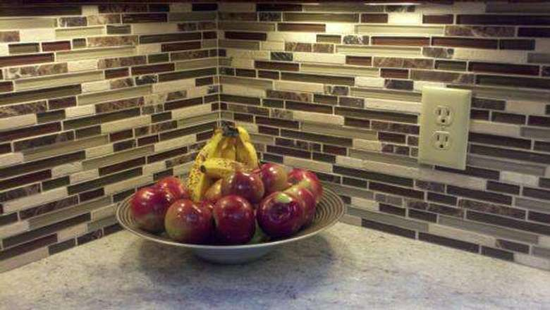 close-up of a tiled backsplash with a bowl of fruit on the counter