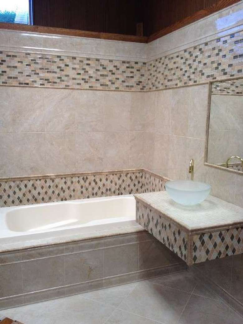 a tiled bathroom with matching accents on the shower walls and vanity