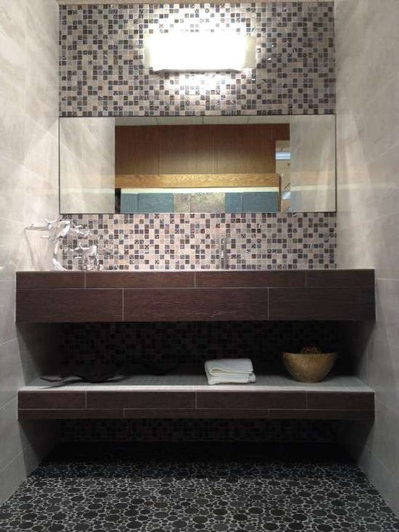 a tiled bathroom with walls, floor, and backsplash using three different types of tiles