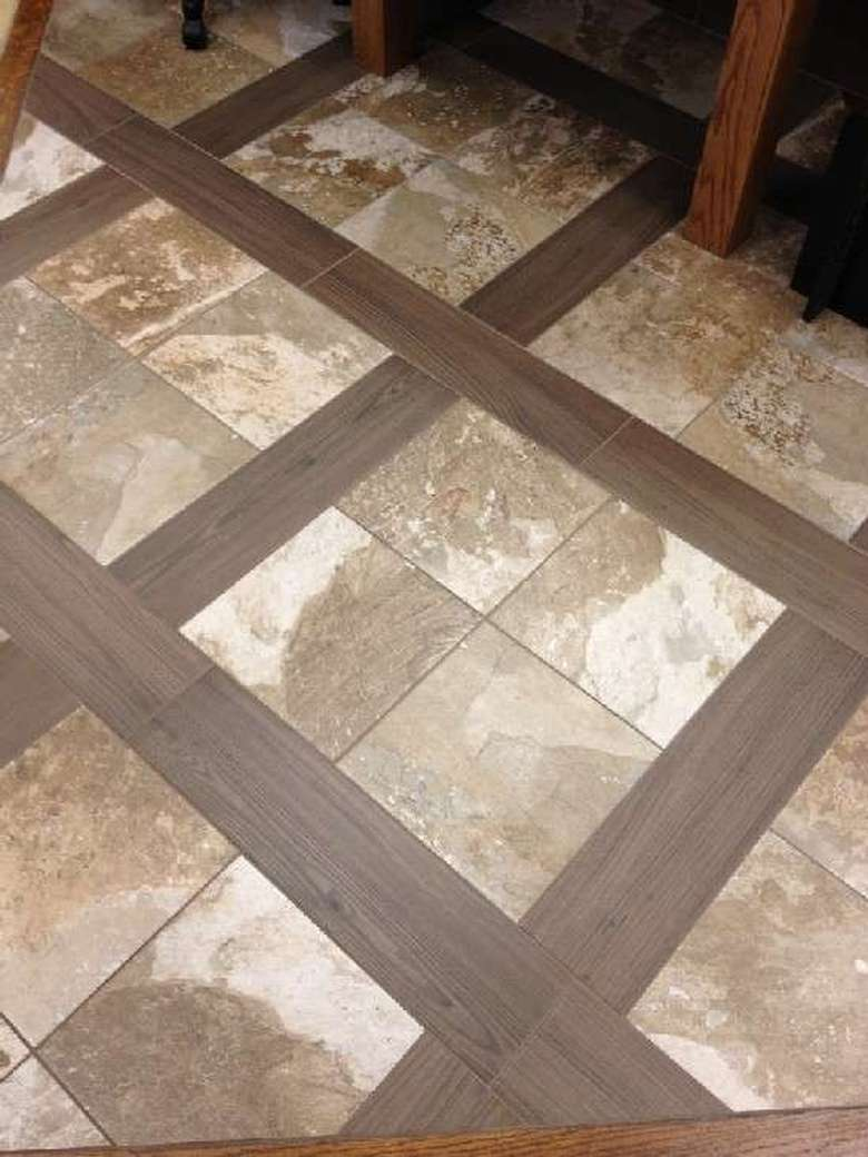 a floor with tiled and wooden accents