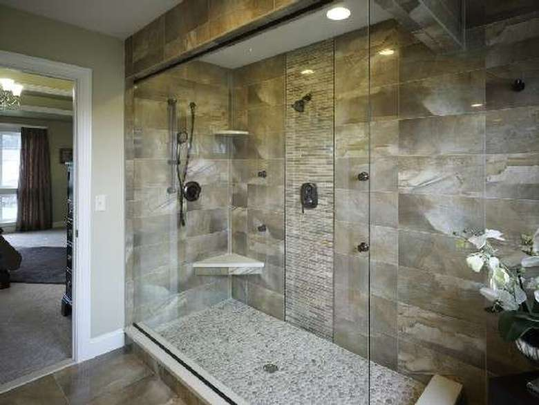 a shower with a mix of tiles and stone with large glass doors