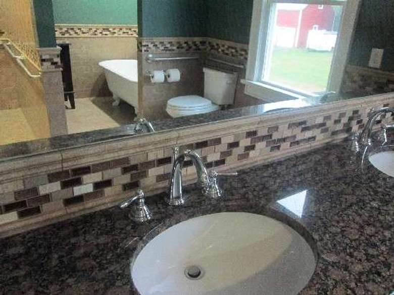 close-up of a stone countertop and tiled backsplash in a bathroom