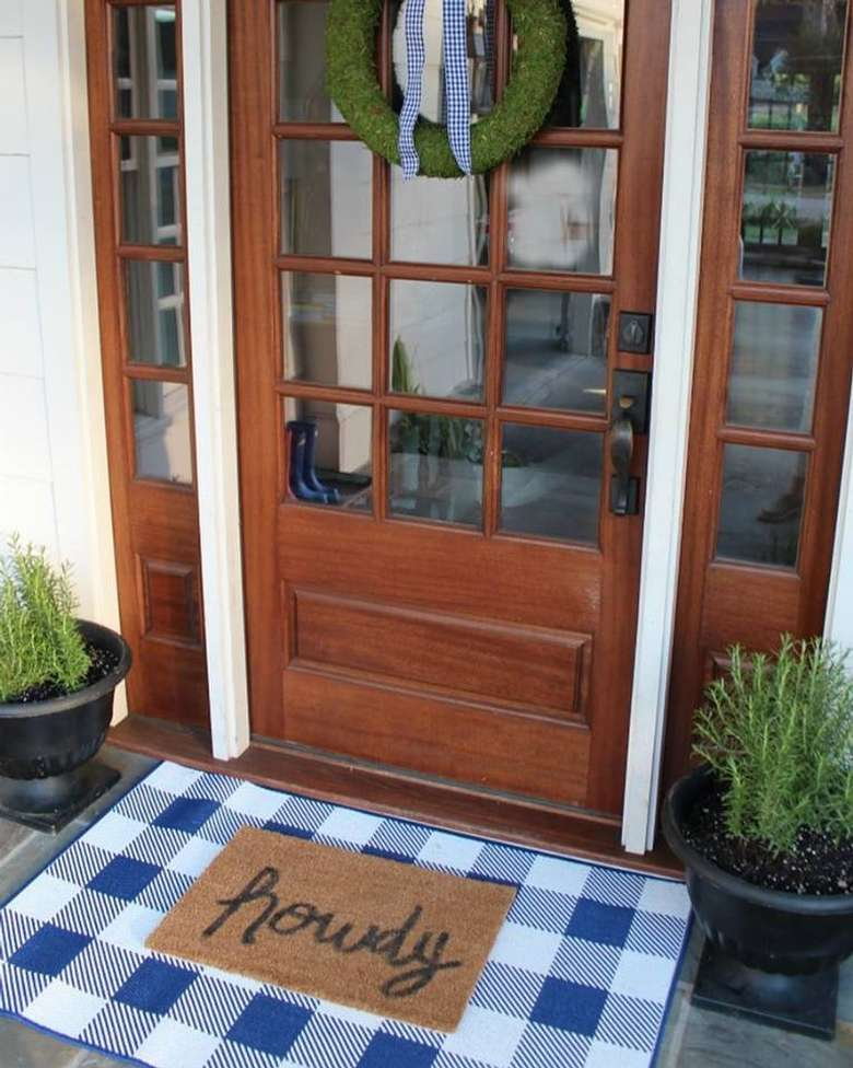 front door with a mat that says howdy