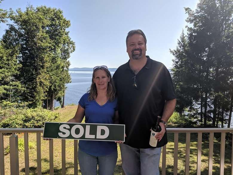 man and woman standing at a house with a sold sign