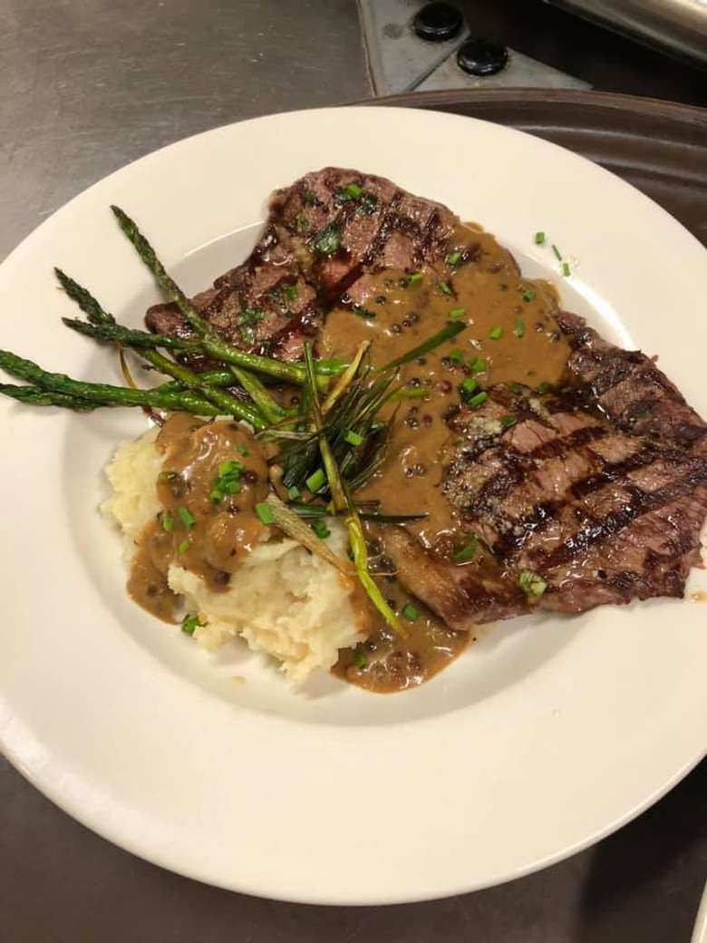 plate of grilled steak, asparagus, and mashed potatoes