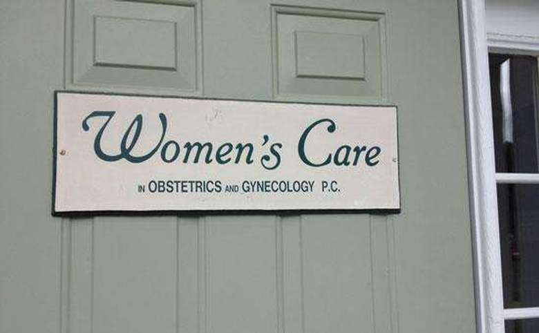 women's care sign on a green door