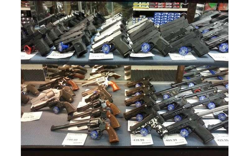 a lot of guns behind a case