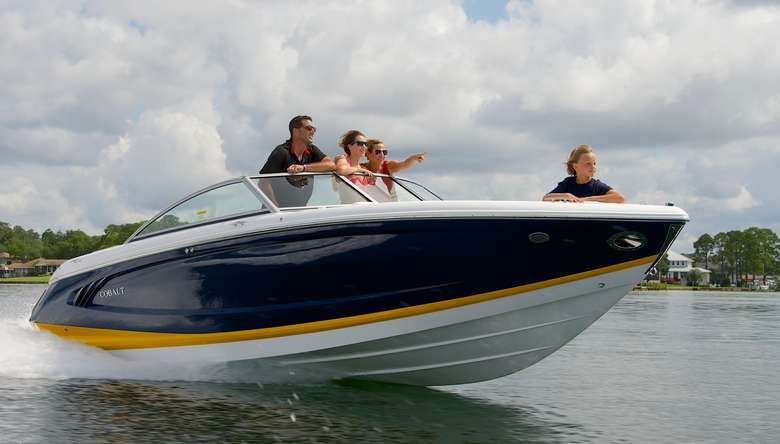 four people in a blue, yellow, and white speedboat