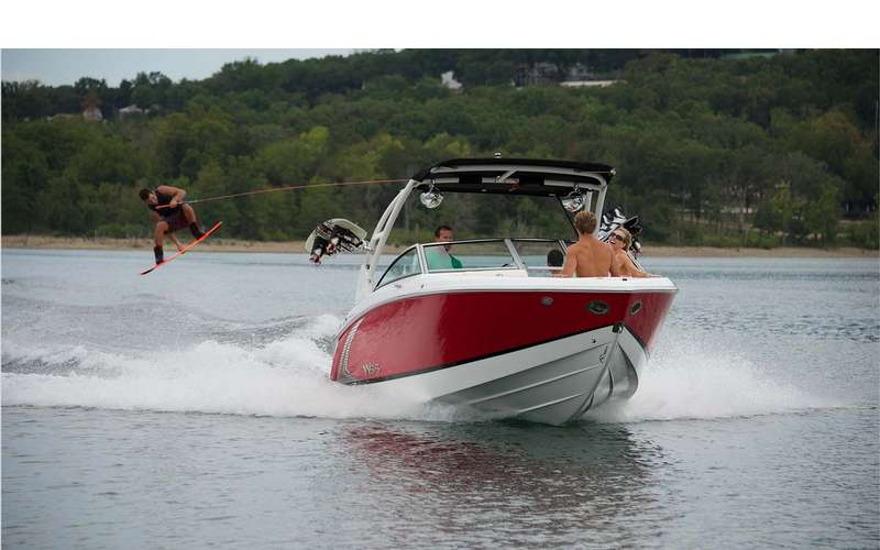 the front of a red and white speedboat with someone skiing off the back