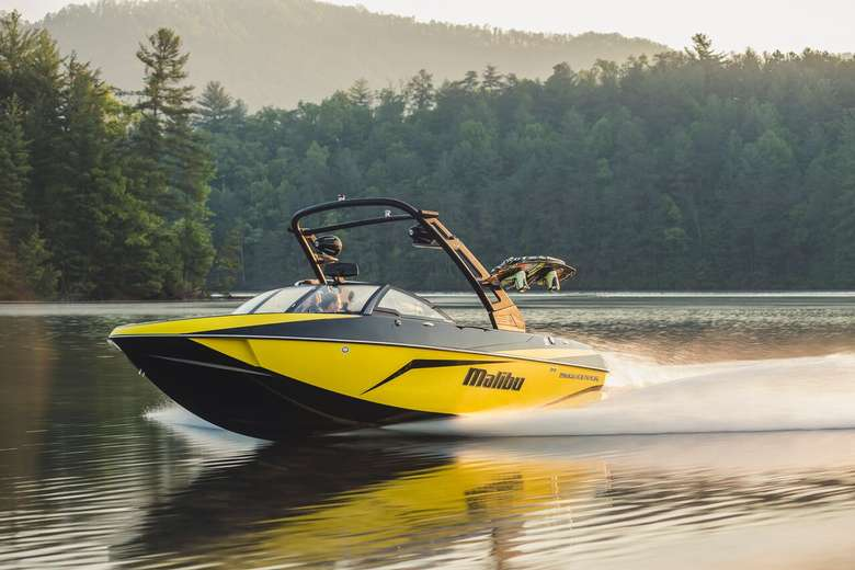 yellow wakeboarding boat in motion
