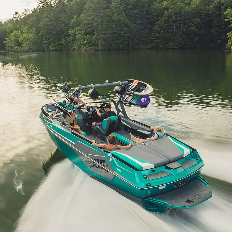 teal wakeboarding boat in motion