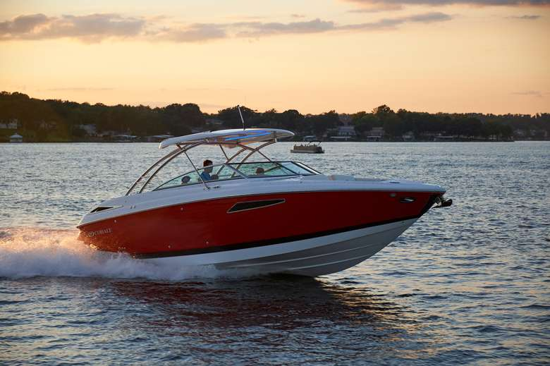 red and white motorboat driving on a lake